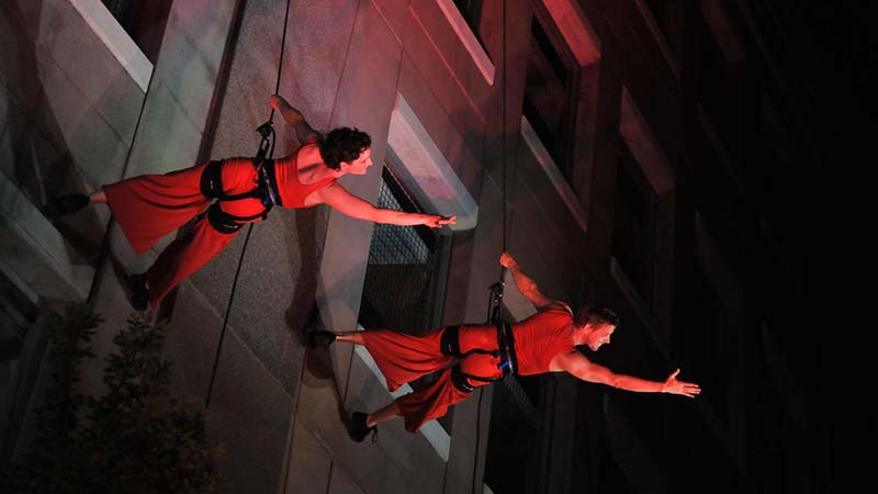 Two theater students repelling off a set